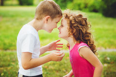 Little brother and sister confronted foreheads. Royalty Free Stock Images