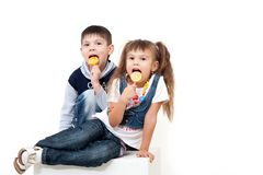 Little brother and sister eating tasty candies Royalty Free Stock Photo