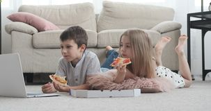 Sibling watching movie at home. Little brother and sister enjoying movie on laptop while having pizza at home stock footage