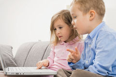 Little brother and sister with laptop Royalty Free Stock Images