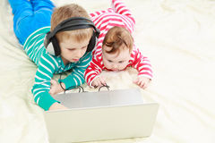 Little brother and sister with laptop at home Stock Images