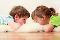 Little brother and sister lying on floor Stock Images