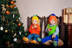 Little brother and sister near Christmas tree Royalty Free Stock Images