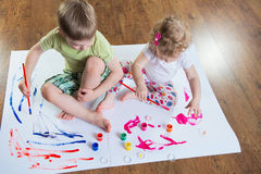 Little brother and sister painting on floor Royalty Free Stock Photo