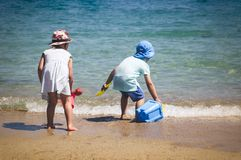 Little brother and sister playing with beach toys on the beach during the family vacation. stock photo