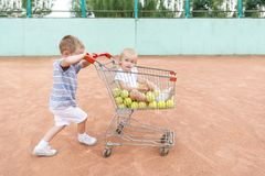 Little children playing at a tennis court with shopping trolley stock photography