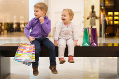 Little brother and sister with shopping bags sitting on bench Royalty Free Stock Photo
