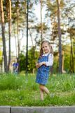 Little brother and the sister sit on a glade with fluffy white dandelions stock photo