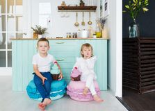 Little brother and sister sit in home kitchen with model ice-cream. Royalty Free Stock Photos