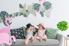 A little brother and sister sits on a sofa in the children`s room. stock photography