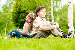 Little brother and sister sitting back to back. Cute little girl and boy, brother and sister, sitting on green grass back to back, smiling and looking in camera Stock Photos