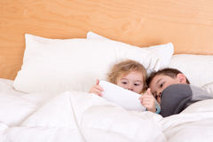 Little brother and sister snuggling up at bedtime Stock Photos