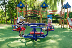 Little brother and sister spinning on roundabout Royalty Free Stock Images