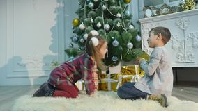Little brother and sister unpack gifts. The concept of Christmas and New Year stock video