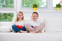 Little brother and sister watching tv Royalty Free Stock Photography