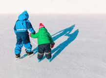 Little brother teaching sister to skate in winter snow. Nature royalty free stock photography