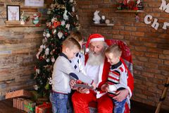Little brothers boys teach Santa Claus to play on tablet in fest Stock Image