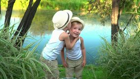 Little brothers go from the coast of the lake after fishing. Children cheerfully walk after rest on. Brothers are stock video