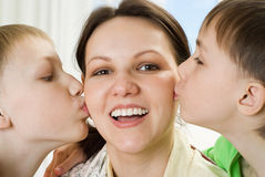 Little brothers kissing his mom Stock Images