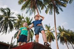 Little brothers look into the distance standing on an old wooden boat. Tropical island. The boys in blue and green stock photo
