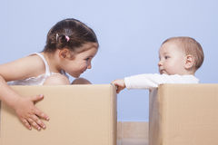Little brothers pplaying with cardboard boxes royalty free stock images