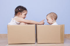 Little brothers pplaying with cardboard boxes Royalty Free Stock Image