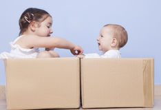 Little brothers pplaying with cardboard boxes Royalty Free Stock Photo