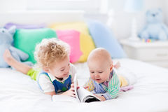 Little brothers reading a book in bed Royalty Free Stock Image
