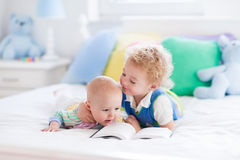 Little brothers reading a book in bed Stock Photo