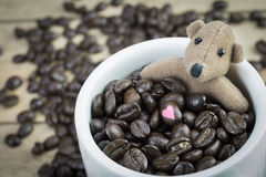 Little brown bear and coffee beans  in white mug Royalty Free Stock Photography