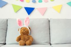 Teddy bear sitting on the sofa in bunny ears bright background stock photo