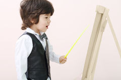 Little brunet boy with yellow pointer stands Royalty Free Stock Image
