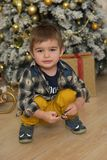 Little brunette boy in a plaid shirt near a Christmas tree. At Christmas royalty free stock image