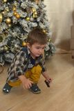 Little brunette boy in a plaid shirt near a Christmas tree. At Christmas stock photo