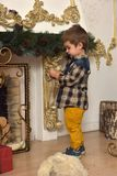 Little brunette boy in a plaid shirt near a Christmas tree. At Christmas stock photography