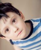 Little brunette boy wearing striped shirt indoor. Brunette boy wearing striped shirt indoor Royalty Free Stock Photos
