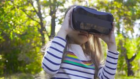 Little brunette caucasian girl in VR glasses staying in the autumn park and smiling. Pretty child trying modern. Technologies outdoors stock footage