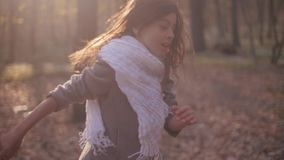 Little brunette girl with a bright scarf and long hair. Scared child is running in rush through the mysterious forest