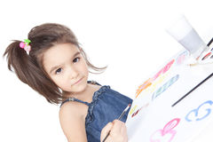 Little brunette girl drawing at the desk Royalty Free Stock Images