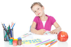 Little brunette girl drawing at the desk Royalty Free Stock Image