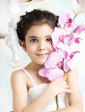 Little brunette girl holding a flower Stock Photos