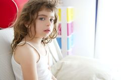 Little brunette girl sit on sofa window light Royalty Free Stock Images
