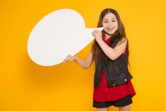 Little brunette girl with speech bubble. Portrait of little cute girl in red shirt holding blank white speech bubble with empty space for text isolated on orange Stock Photo