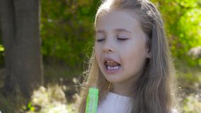 Little brunette girl staying in autumn sunrays and blowing soap bubbles. Little child in striped jacket imitating. Licking the bottle and laughing stock video footage