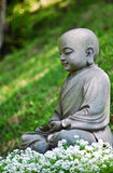 Little Buddah. A statue of Buddah over the flowers royalty free stock photography