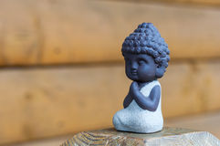 Little Buddha pray or meditate on wooden background with empty space. Praying and meditation, yoga concept Royalty Free Stock Images