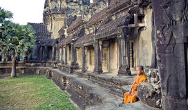Little Buddhist monk in the ruins of Angkor. Angkor Wat, the central entrance to the historic complex. 20.11.2009 year: Stock Image