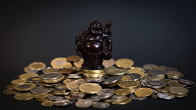Little Budha statue on a pile of coins. Little Buddha statue sitting on a big pile of coins bringing good luck Royalty Free Stock Photography