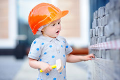Little builder in hardhats with hammer working outdoors Stock Images
