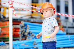 Little builder in hardhats with hammer working outdoors Stock Photography